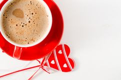 Une tasse rouge de cappuccino avec le coeur en bois sur le Tableau rustique léger Photos libres de droits