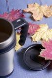 Une tasse thermo, se tenant sur un tissu gris Il est répandu avec les feuilles d'automne tombées de différentes couleurs images stock