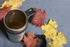 Une tasse thermo, se tenant sur un tissu gris Il est répandu avec les feuilles d'automne tombées de différentes couleurs photographie stock libre de droits