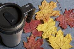 Une tasse thermo, se tenant sur un tissu gris Il est répandu avec les feuilles d'automne tombées de différentes couleurs image stock