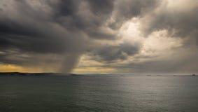 Une tempête en mer devant la ville Photos stock