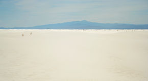 Une tentative d'homme et de femme de croiser les sables blancs Images libres de droits