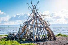 Une tente de bois de flottage a photographié sur la plage en Tamise Coromandel photos libres de droits