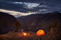 Une tente et un feu de camp lumineux en montagnes dans l'aube Images stock