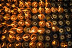Une terre des bougies brûlantes s'allumant au temple bouddhiste Image libre de droits