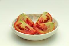 Une tomate rouge dans quatre paix dans une cuvette Photo stock