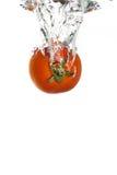 Une tomate tombant dans l'eau photographie stock