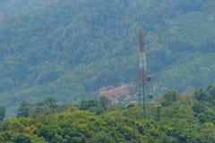 Une tour grande de télécommunication se tient dedans parmi le vert val Image libre de droits