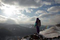Une touriste seule de jeune femme se tient au bord d'une falaise et apprécie le paysage des montagnes images stock