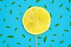 Une tranche de citron coupé en tranches sur un bâton Fond bleu avec des feuilles Fruits juteux frais Fond de fruit photos libres de droits