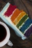 Une tranche de gâteau d'arc-en-ciel avec une tasse de café Images libres de droits