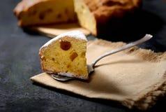 Une tranche de gâteau fraîchement cuit au four sur une cuillère sur une serviette de toile sur un fond noir photos stock