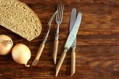Une tranche de pain de seigle, d'oignons et de couverts Image stock