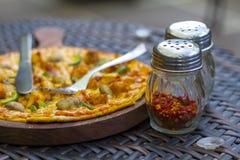 Une tranche de pizza dans le plat, les fourchettes et le couteau Photographie stock libre de droits