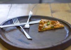 Une tranche de pizza dans le plat, les fourchettes et le couteau Images stock