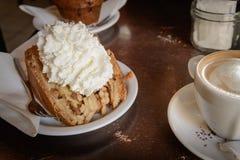 Une tranche de tarte aux pommes avec la crème fouettée et un café de cappuccino sur une table en bois photo libre de droits