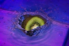 Une tranche en baisse de kiwi dans l'eau gentille Photographie stock libre de droits
