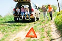Une triangle de panne se tient près d'un automobile cassé de la route photo stock