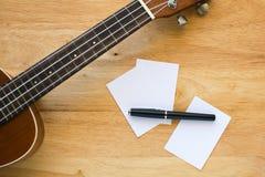 Une ukulélé sur le bureau en bois, ton chaud, haut étroit d'ukulélé, musique concentrée Photos stock