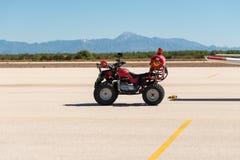 Une urgence et une délivrance rouges de tablier ont équipé le vélo de quadruple attendant sur la piste d'aéroport Images libres de droits