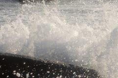 Une vague de fentes de jet au sujet d'un rocher Images libres de droits