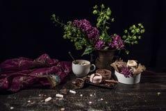Une vieille écharpe transparente pourpre débordante dans le style oriental sur une table en bois avec du café Photo stock