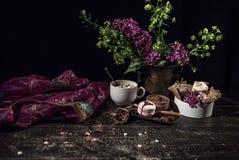 Une vieille écharpe transparente pourpre débordante dans le style oriental sur une table en bois avec du café Photographie stock