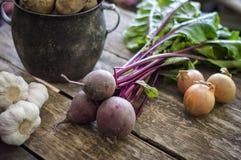 Une vieille betterave d'ail d'oignon de pomme de terre de pot sur le vieux fond de conseil Photographie stock