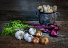 Une vieille betterave d'ail d'oignon de pomme de terre de pot sur le vieux fond de conseil Photographie stock libre de droits