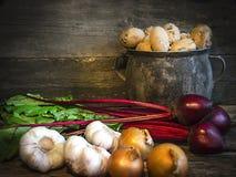 Une vieille betterave d'ail d'oignon de pomme de terre de pot sur le vieux fond de conseil Photo libre de droits
