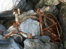 Une vieille bicyclette rouillée jetée dans les pierres Image stock
