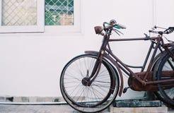 Une vieille bicyclette se penche contre le mur Photo libre de droits