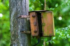 Une vieille boîte de jonction électrique rouillée sur un poteau en bois Photos libres de droits