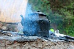 Une vieille bouilloire de l'eau sur la cheminée photos stock