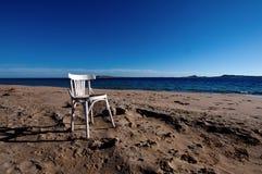 Une vieille chaise blanche vide sur une plage sablonneuse la Mer Rouge photographie stock libre de droits