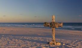 Une vieille croix sur la dune de sable à côté de l'océan avec un lever de soleil calme Image libre de droits
