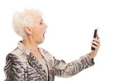 Une vieille dame élégante à l'aide du téléphone portable. Photographie stock libre de droits