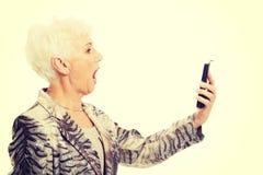 Une vieille dame élégante à l'aide du téléphone portable Images libres de droits