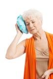Une vieille dame avec le sac de glace par sa tête. Photographie stock