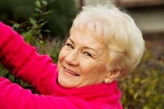 Une vieille dame coupe des buissons. image stock