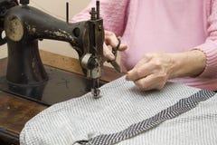 Une vieille femme de cheveux blancs coud sur une vieille machine à coudre Mise sur pied d'une vieille femme d'ouvrière couturière Images stock