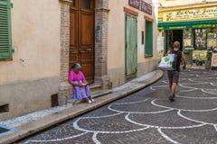 Une vieille femme de couleur lisant un livre se reposant sur des escaliers photos libres de droits
