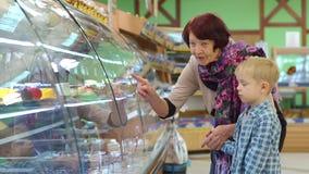 Une vieille grand-m?re avec un petit petit-fils dans le supermarch? choisissent des bonbons banque de vidéos