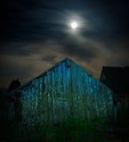 Une vieille grange en bois fantasmagorique la nuit illuminé avec la pleine lune Photo libre de droits