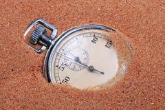 Une vieille horloge dans le sable. Photographie stock