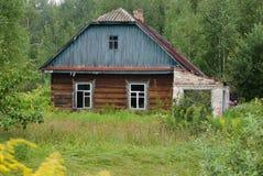 Une vieille maison abandonnée avec les fenêtres cassées dans la campagne Position dans les buissons et les arbres épais Image libre de droits