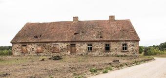 Une vieille maison en pierre abandonnée avec un toit carrelé dans le village images libres de droits
