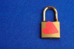 Une vieille serrure de protection rouillée décorée d'un coeur rouge Photos stock