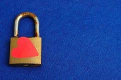 Une vieille serrure de protection rouillée décorée d'un coeur rouge Photo stock