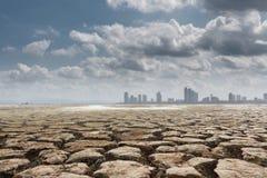 Une ville regarde au-dessus d'une terre criquée photos libres de droits